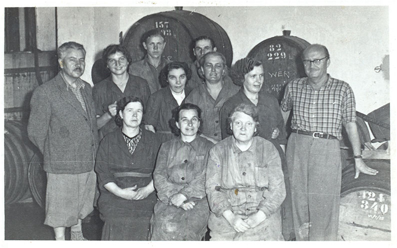 Jan Wojnarowicz (first from the left) and Ryszard Siwiec – former co-owners of the Wine and Honey Manufacturing – with employees, August 1959